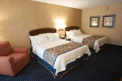 Our Standard Double Queen Bed Rooms Feature Fresh-daily Linens Sitting Chair And Work Desk. 3 of 10